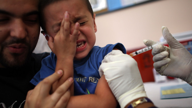 HIALEAH, FL - AUGUST 08:  Michael Valdivia holds, Jakob Gutierrez, 5, as he receives an immunization shot from school nurse Barbara Dale on August 8, 2007 in Hialeah, Florida. The free immunization is part of the Miami-Dade County Health Department's program to help children heading back to school.  (Photo by Joe Raedle/Getty Images)