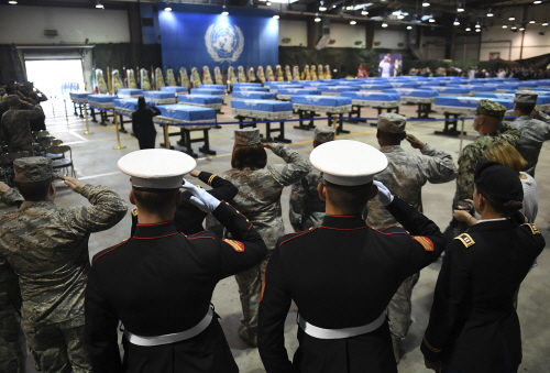 U.S. soldiers salute during a repatriation ceremony for the remains of U.S. soldiers who were killed in the Korean War and collected in North Korea, at the Osan Air Base in Pyeongtaek, South Korea, Wednesday, Aug. 1, 2018. North Korea handed over 55 boxes of the remains last week as part of agreements reached during a historic June summit between its leader Kim Jong Un and U.S. President Donald Trump. (Jung Yeon-je/Pool Photo via AP)