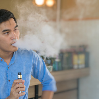 Handsome guy smoking electronic cigarette smoke in outdoor cafe.