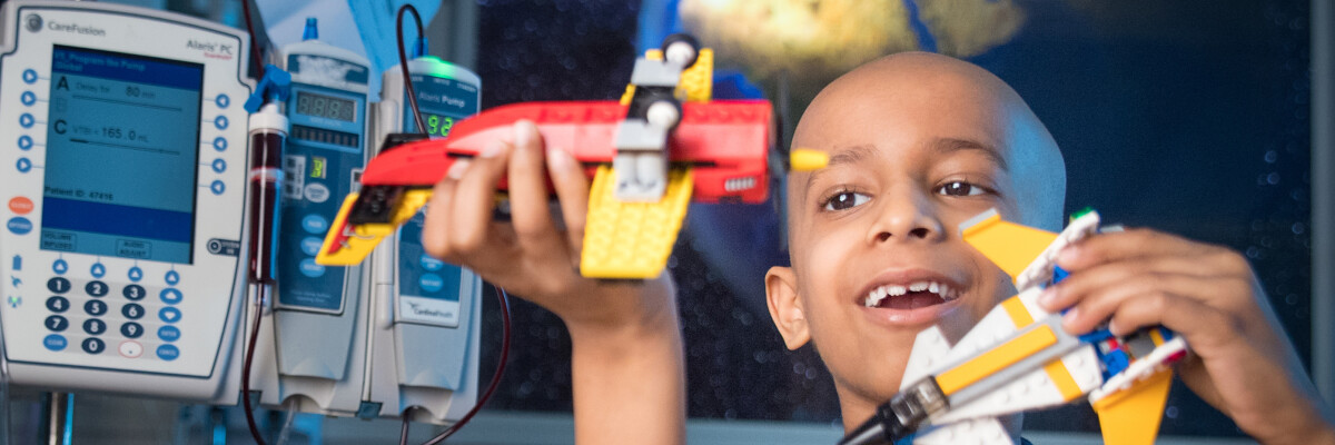 St. Jude patient Zahaan, seen here at age 7 in 2017, plays with a plane and rocketship toy at St. Jude Children's Research Hospital